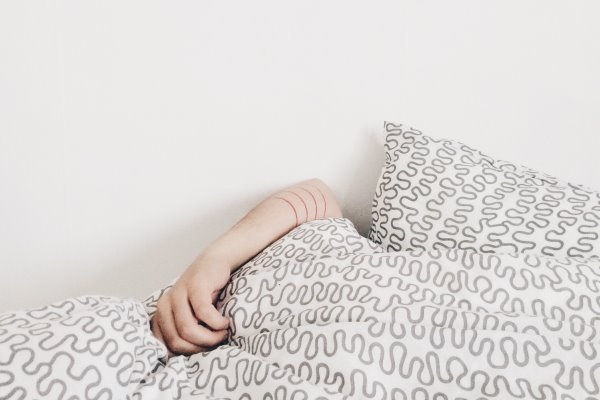 arm peeking at bed sheets and pillows
