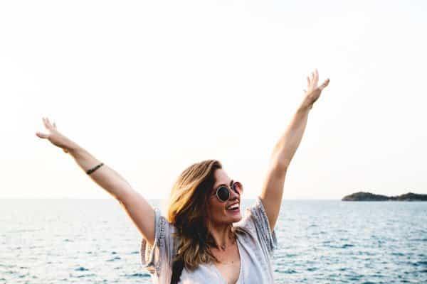 happy woman raising her arms; ocean backdrop