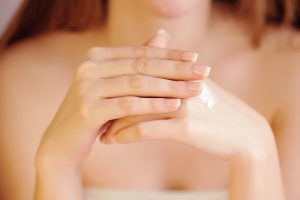Young woman applies cream on her hands after bath. Focus on hands