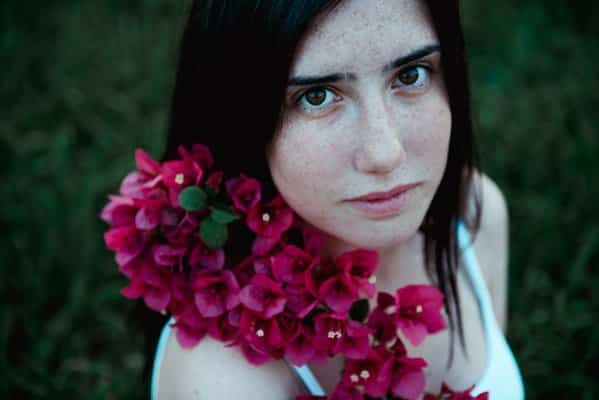 Pretty freckled woman holding flowers