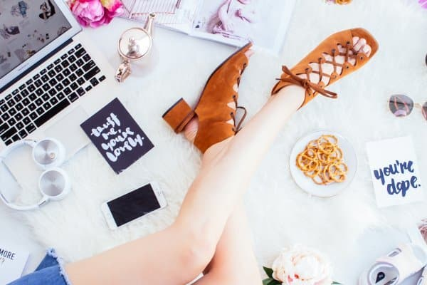 flat lay shot of a girl lying on bed with laptop, pretzels, notebooks, smartphone, etc. (close up on legs)