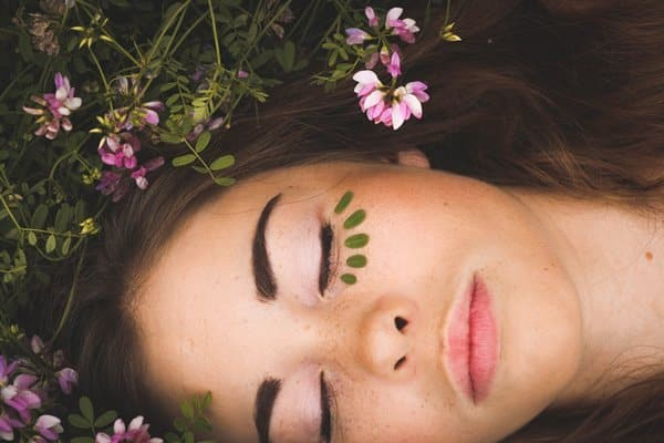 close up shot of a girl laying on flowers and grass