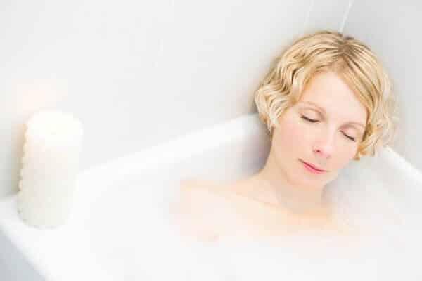 A woman soaking her skin in a bubble bath