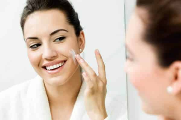 Woman applying a serum to her face