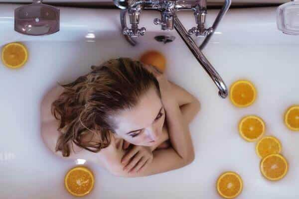 Girl taking a relaxing bath in milk and oranges