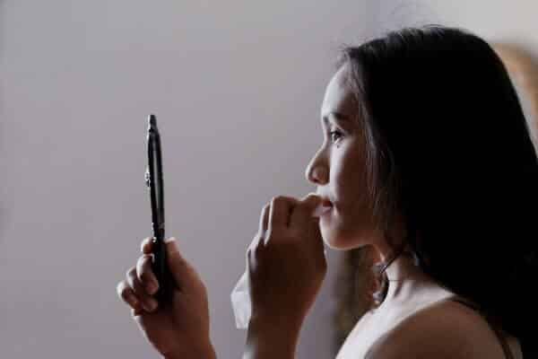 Girl checking the mirror for blemishes